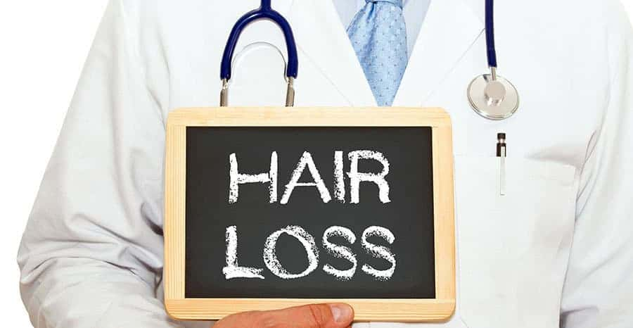 Doctor holding a signboard with the text, *HAIR LOSS*