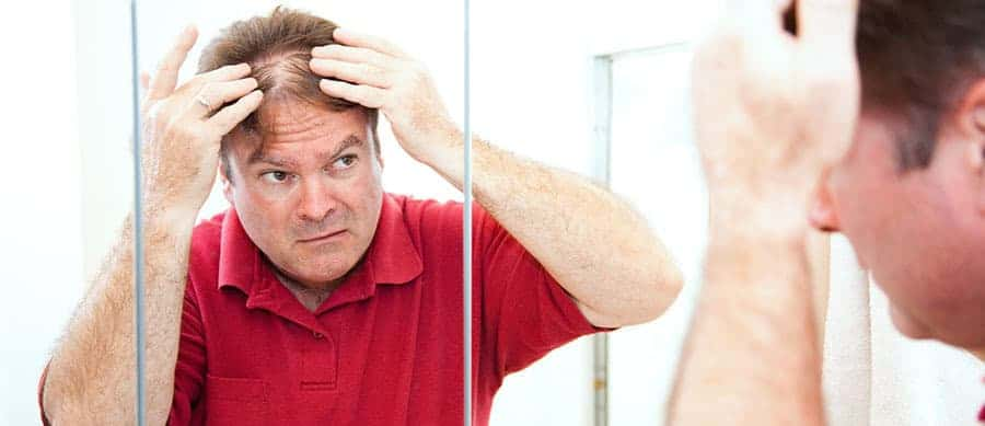 Middle aged man looking at his hair in the mirror.