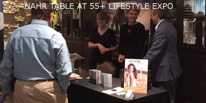 Man and Woman chattering at a Expo. With text*NAHR TABLE AT 55+ lIFESTYE EXPO