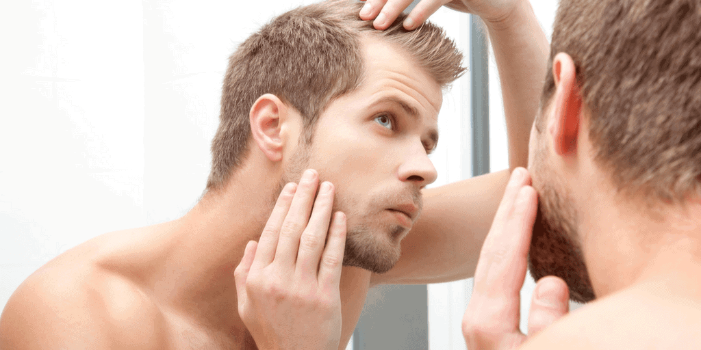 Men checking his sideburns on a mirror