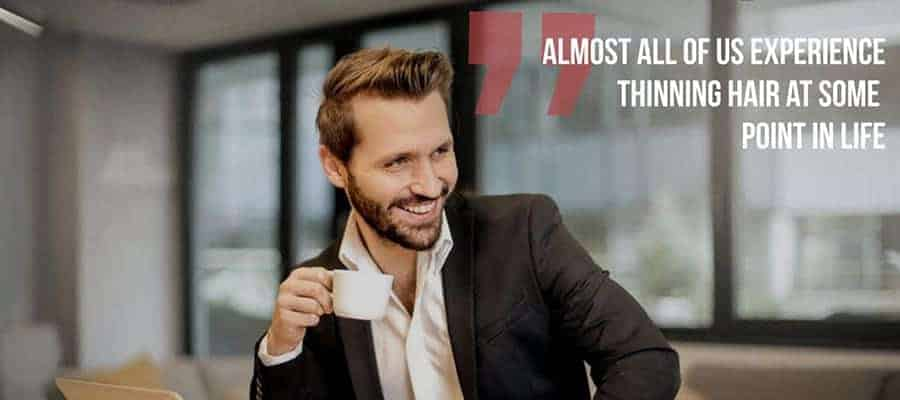 """a smiling guy in a suite holding a white cup with a text, """"Almost all of us experience thinning hair at some point in life"""""""